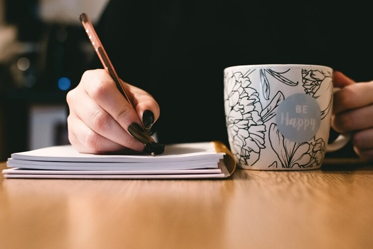 woman writing on paper holding a mug in other hand
